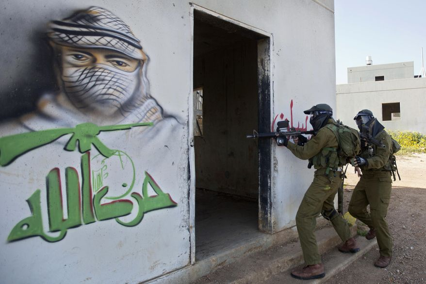 """In this Wednesday, March 29, 2017 photo, Israeli soldiers train with paintball guns during a drill at an Army base near Elyakim, Israel. Between myriad concrete buildings with Arabic graffiti that are designed to simulate a typical Lebanese village, dozens of Israeli officers are gearing up for their next battle with Hezbollah guerrillas. The drill at a base in northern Israel takes on added significance in the wake of rising tensions between the old adversaries. Arabic reads, """"Hezbollah."""" (AP Photo/Sebastian Scheiner)"""