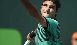 Roger Federer, of Switzerland, serves to Tomas Berdych, of the Czech Republic, at the Miami Open tennis tournament, Thursday, March 30, 2017, in Key Biscayne, Fla. Federer defeated Berdych 6-2, 3-6, 7-6 (6). (AP Photo/Wilfredo Lee)
