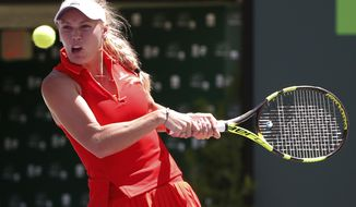 Caroline Wozniacki, of Denmark, returns a shot from Karolina Pliskova, of the Czech Republic, during a tennis match at the Miami Open, Thursday, March 30, 2017 in Key Biscayne, Fla. (AP Photo/Wilfredo Lee)