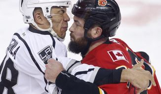 Los Angeles Kings' Jarome Iginla, left, fights with Calgary Flames' Deryk Engelland during the first period of an NHL hockey game in Calgary, Alberta, Wednesday, March 29, 2017. (Larry MacDougal/The Canadian Press via AP)