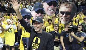 FILE - In this Feb. 1, 2014, file photo, Nike's Phil Knight acknowledges the crowd on Uncle Phil Appreciation Night at Matthew Knight Arena during Oregon's NCAA college basketball game against Southern California in Eugene, Ore. It's one thing to have Nike as a shoe sponsor. It's quite another to have the owner of Nike as your main benefactor.  (AP Photo/Chris Pietsch, File)