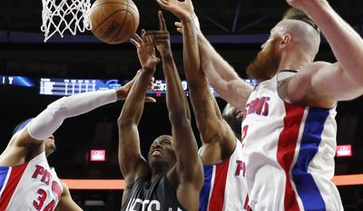 Brooklyn Nets guard Isaiah Whitehead, center, goes up for the rebound with Detroit Pistons forward Tobias Harris (34), center Aron Baynes (12) and forward Marcus Morris, rear, during the first half of an NBA basketball game, Thursday, March 30, 2017, in Auburn Hills, Mich. (AP Photo/Carlos Osorio)