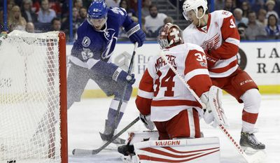 Tampa Bay Lightning defenseman Andrej Sustr (62) shoots the puck past Detroit Red Wings goalie Petr Mrazek (34) and defenseman Nick Jensen (3) for a goal during the second period of an NHL hockey game Thursday, March 30, 2017, in Tampa, Fla. (AP Photo/Chris O'Meara)