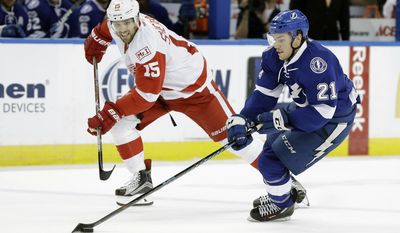 Tampa Bay Lightning center Brayden Point (21) stick-handles around Detroit Red Wings center Riley Sheahan (15) during the second period of an NHL hockey game Thursday, March 30, 2017, in Tampa, Fla. (AP Photo/Chris O'Meara)