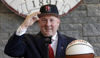 New Seattle University NCAA college head basketball coach Jim Hayford gamely pulls on a school ball cap at an introduction event for him Thursday, March 30, 2017, in Seattle. Hayford was previously the head coach at Eastern Washington. (AP Photo/Elaine Thompson)
