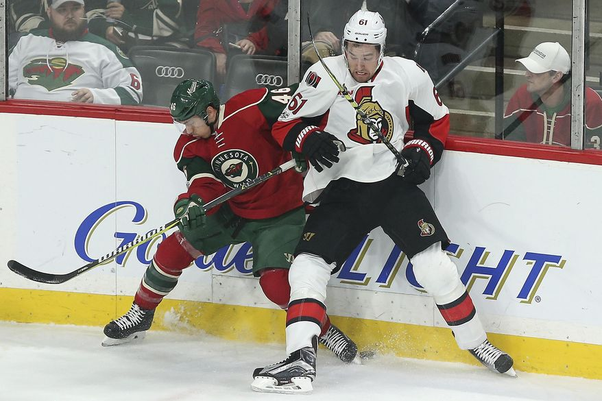 Minnesota Wild's Jared Spurgeon (46) and Ottawa Senators' Mark Stone (61) scramble to find the puck in the first period of an NHL hockey game Thursday, March 30, 2017, in St. Paul, Minn. (AP Photo/Stacy Bengs)