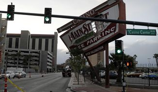 High winds damaged a sign for the Main Street Station casino, Thursday, March 30, 2017, in Las Vegas. A fast-moving, windy cold front shook Nevada from top to bottom Thursday, dropping snow in the mountains around Lake Tahoe, toppling trucks and downing power lines resulting in widespread outages around Las Vegas. (AP Photo/John Locher)