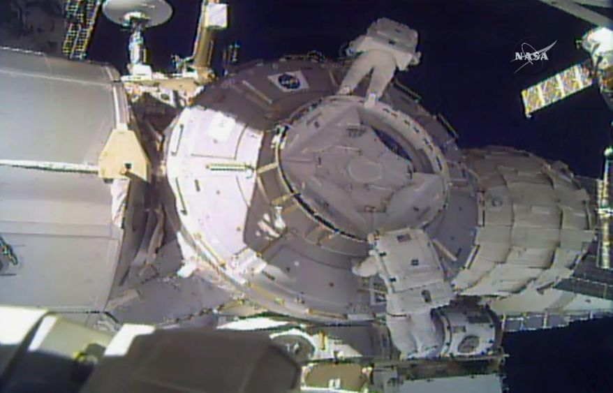 In this image made from video provided by NASA, U.S. astronauts Peggy Whitson, above, and Shane Kimbrough work on the outside of the International Space Station on Thursday, March 30, 2017. An important piece of micrometeorite shielding was lost during the spacewalk. (NASA via AP)