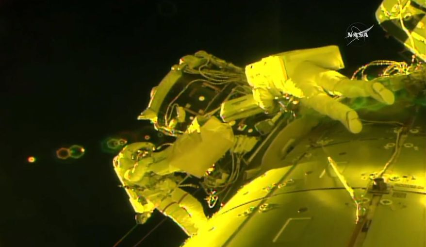 In this image made from video provided by NASA, U.S. astronauts Shane Kimbrough, left, and Peggy Whitson, install a shield on a relocated docking port outside of the International Space Station on Thursday, March 30, 2017. An important piece of micrometeorite shielding was lost during the spacewalk at another part of the station earlier in the day. (NASA via AP)