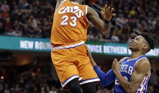 Cleveland Cavaliers' LeBron James, left, dunks the ball against Philadelphia 76ers' Richaun Holmes in the first half of an NBA basketball game, Friday, March 31, 2017, in Cleveland. (AP Photo/Tony Dejak)