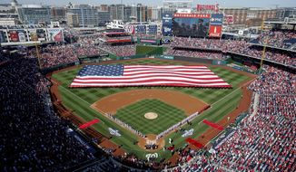 FILE - In this April 6, 2015, file photo, a large American flag is unfurled on the field before a baseball game between the Washington Nationals and the New York Mets on opening day at at Nationals Park, in Washington. Over two-thirds of all major league teams now play in facilities that opened in 1992 or later, part of a ballpark boom that has changed how fans and players experience the game _ and has led to some contentious debate over how to pay for it all.  (AP Photo/Andrew Harnik, File)