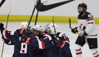 United States forward Brianna Decker, center, is surrounded by teammates after scoring during the second period of a IIHF Women's World Championship hockey tournament game against Canada, Friday, March 31, 2017, in Plymouth, Mich. In the background right is Canada forward Blayre Turnbull. (AP Photo/Carlos Osorio)