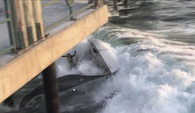 In this Thursday, March 30, 2017, video image courtesy of Jason Wells shows a boat capsized before crashing into the Redondo Beach Pier, in Redondo Beach, Calif. All four people on board were thrown into the water, narrowly missing the pilings, and the boat broke in half. The captain of the boat and another man were taken to the hospital after the wreck Thursday evening, one with a dislocated shoulder and the other complaining of back pain, said Rob Rappaport, a division chief at the Redondo Beach Fire Department. (Jason Wells via AP)