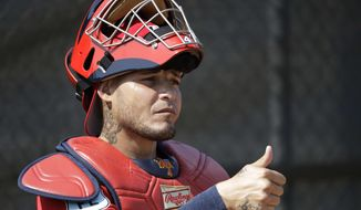 "FILE - In this Feb. 14, 2017, file photo, St. Louis Cardinals catcher Yadier Molina gives a thumbs-up to a pitcher during a spring training baseball workout in Jupiter, Fla. Cardinals general manager John Mozeliak said he's ""hopeful"" to have a new contract for Molina before opening day but said a deal was ""not done"" as of Thursday night, March 30. Molina homered in a game against St. Louis' top minor league affiliate while reports surfaced that he's nearing a new contract agreement. Fox Sports reported during the game that Molina and the Cardinals are finalizing a three-year deal worth between $55 million and $65 million. (AP Photo/David J. Phillip, File)"