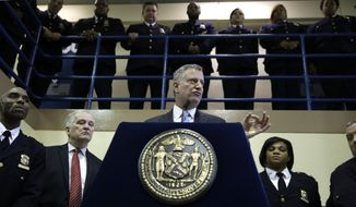 In this March 12, 2015, file photo, surrounded by corrections officers, New York City Mayor Bill de Blasio holds a news conference on Rikers Island in New York. The mayor announced on Friday, March 31, 2017, that he's developing a plan to shut down the massive jail within 10 years. (AP Photo/Seth Wenig, File)