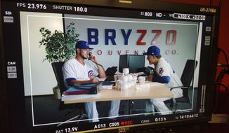This image provided by Major League Baseball shows Chicago Cubs baseball players Kris Bryant, left, and Anthony Rizzo, while shooting a commercial for the mock Bryzzo Souvenir Company in Mesa, Ariz., Wednesday, February, 22 2017. Bryant and Rizzo had a big hit with their Bryzzo Souvenir Company commercials last season and are stepping up their game for this year's spots. (MLB via AP)