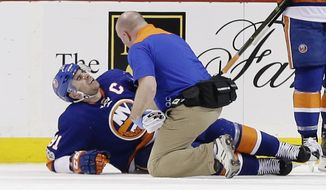 A trainer checks on New York Islanders' John Tavares after he was injured during the third period of an NHL hockey game against the New Jersey Devils Friday, March 31, 2017, in New York. The Islanders won 2-1. (AP Photo/Frank Franklin II)