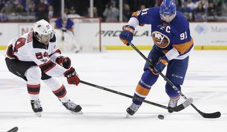 New Jersey Devils' Joseph Blandisi (64) and New York Islanders' John Tavares (91) fight for the puck during the second period of an NHL hockey game Friday, March 31, 2017, in New York. (AP Photo/Frank Franklin II)