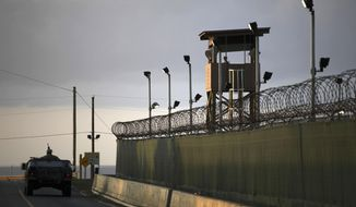 In this March 30, 2010, file photo, reviewed by the U.S. military, a U.S. trooper stands in the turret of a vehicle with a machine gun, left, as a guard looks out from a tower at the detention facility of Guantanamo Bay U.S. Naval Base in Cuba. (AP Photo/Brennan Linsley, File)