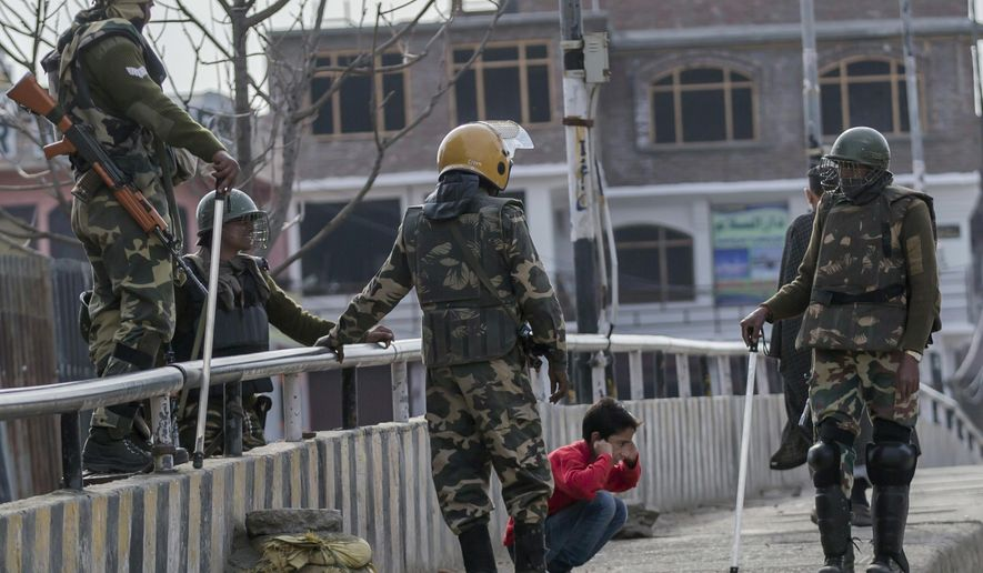 FILE - In this March 29, 2017, file photo, Indian paramilitary soldiers force a Kashmiri child to perform sit-up while holding his ear lobes, a common elementary school punishment in India, before letting him go during a strike in Srinagar, Indian-controlled Kashmir. Seeing Kashmiri residents doing calisthenics on the side of the road was once common in the 1990s, as government forces sought to humiliate people as a way of dissuading any support for armed rebels fighting against Indian rule in the disputed Himalayan territory. As the rebellion was crushed, Indian soldiers mostly stopped using public sit-ups as a form of punishment. (AP Photo/Dar Yasin, File)