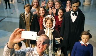 FILE - In Jan. 11, 2015 file photo, then Illinois Governor-elect Bruce Rauner takes a selfie with his family and statues of the Lincoln family, at the Abraham Lincoln Museum and Library in Springfield, Ill. Gov. Rauner has signed an executive order making the Lincoln Presidential Library and Museum a separate state agency. The Friday March 31, 2017 order means that the Springfield museum will no longer fall under the Illinois Historic Preservation Agency. (AP Photo/Charles Rex Arbogast, File)