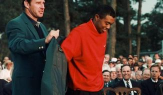 In this April 13,1997, file photo, Tiger Woods, 1997 Masters champion, receives his Green Jacket from the previous year's winner Nick Faldo, left, at the Augusta National Golf Club in Augusta, Ga. It has been 20 years since Woods won the Masters for the first time by a record 12 shots. (AP Photo/Amy Sancetta, File)