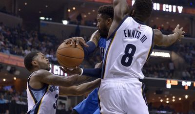 Dallas Mavericks guard Wesley Matthews, center, looks to pass between Memphis Grizzlies forward James Ennis (8) and guard Troy Daniels, left, in the first half of an NBA basketball game Friday, March 31, 2017, in Memphis, Tenn. (AP Photo/Brandon Dill)