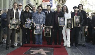 FILE - In this Jan. 21, 2005, file photo, members of the band Journey pose after receiving a star on the Hollywood Walk of Fame in Los Angeles. Keyboardist Jonathan Cain told the Dayton Daily News for a story published online on March 30, 2017, that former singer Steve Perry will be in attendance when the band is inducted into the Rock and Roll Hall of Fame on April 7, 2017. (AP Photo/Nick Ut, File)