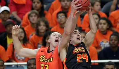 East team's Josh Hawkinson (33) fights for a rebound with West team's Tyler Cavanaugh (24) during the first half of the NCAA All-Star game Friday, March 31, 2017, in Glendale, Ariz. (AP Photo/Matt York)