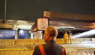 Firefighters survey the section of an overpass that collapsed from a large fire on Interstate 85 in Atlanta, Thursday, March 30, 2017. Atlanta officials say a massive fire that burned for more than an hour caused the collapse of the interstate overpass. Georgia Gov. Nathan Deal has issued a state of emergency for the county. (AP Photo/David Goldman)