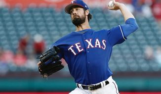 Texas Rangers starting pitcher Cole Hamels throws during the first inning of an exhibition baseball game against the Kansas City Royals, Friday, March 31, 2017, in Arlington, Texas. (AP Photo/Brandon Wade)