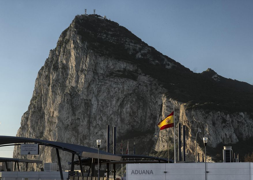 FILE- In this Wednesday, March 1, 2017 file photo, a Spanish flag flies on top of the customs house on the Spanish side of the border between Spain and the British overseas territory of Gibraltar with the Rock as a background, in La Linea de la Concepcion, Southern Spain. The EU's roadmap on Brexit negotiations leaves the U.K. and Spain to discuss what agreements will apply to Gibraltar, a dialogue in which Madrid could have the upper hand. (AP Photo/Daniel Ochoa de Olza, File)