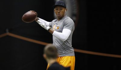 Quarterback Josh Dobbs plays with a young boy before competing Tennessee NFL Pro Day on Friday, March 31, 2017, in Knoxville, Tenn. (AP Photo/Wade Payne)