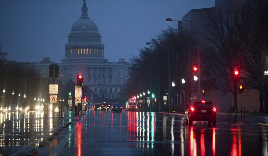 Capitol Hill is seen on the distance as rain falls on Pennsylvania Avenue in Washington, early Friday, March 31, 2017. (AP Photo/J. Scott Applewhite)