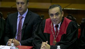 Venezuela's Vice-President Tareck El Aissami, left, and Supreme Court President Maikel Moreno during a meeting with Ambassadors from different countries and Diplomatics at the Supreme Court in Caracas, Venezuela, Saturday, April 1, 2017. Venezuela's president and Supreme Court backed down Saturday from an audacious move to strip congress of its legislative powers that had sparked widespread charges that the South American country was no longer a democracy. (AP Photo/Ariana Cubillos)