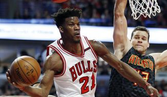 Chicago Bulls guard/forward Jimmy Butler (21) looks to pass past Atlanta Hawks guard Kent Bazemore, left, and forward Kris Humphries during the first half of an NBA basketball game Saturday, April 1, 2017, in Chicago. (AP Photo/Nam Y. Huh) **FILE**