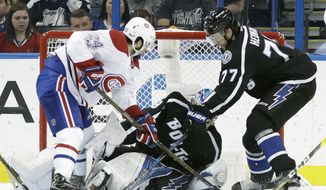 Montreal Canadiens left wing Phillip Danault (24) tucks the past Tampa Bay Lightning goalie Andrei Vasilevskiy (88) and defenseman Victor Hedman (77) for a goal during the second period of an NHL hockey game Saturday, April 1, 2017, in Tampa, Fla. (AP Photo/Chris O'Meara)