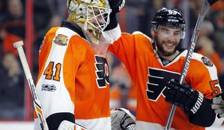 Philadelphia Flyers goalie Anthony Stolarz, left and teammate Shayne Gostisbehere celebrate the team's 3-0 win over the New Jersey Devils in an NHL hockey game Saturday, April 1, 2017, in Philadelphia. (AP Photo/Tom Mihalek)
