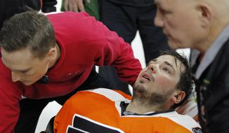 Philadelphia Flyers goalie Michal Neuvirth is taken off the ice on a stretcher after collapsing to the ice early in the first period of the team's NHL hockey game against the New Jersey Devils, Saturday, April 1, 2017, in Philadelphia. (AP Photo/Tom Mihalek)
