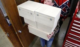 FOR RELEASE SATURDAY, APRIL 1, 2017, AT 12:01 A.M. CDT.- Freshman Deric Trees carries soft maple boxes the student designed and built for patients at the U of I Children's Hospital in their industrial tech class at Clarksville high school Monday, March 20, 2017, in Clarksville, Iowa. (Matthew Putney /The Courier via AP)