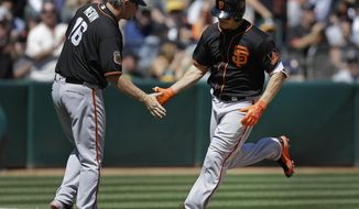 San Francisco Giants' Nick Hundley, right, is congratulated by third base coach Phil Nevin (16) after hitting a grand slam off Oakland Athletics' Andrew Triggs in the fourth inning of an exhibition baseball game Saturday, April 1, 2017, in Oakland, Calif. (AP Photo/Ben Margot)