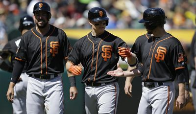 San Francisco Giants' Nick Hundley, center, is congratulated by Aaron Hill, right, after hitting a grand slam off Oakland Athletics' Andrew Triggs in the fourth inning of an exhibition baseball game Saturday, April 1, 2017, in Oakland, Calif. (AP Photo/Ben Margot)