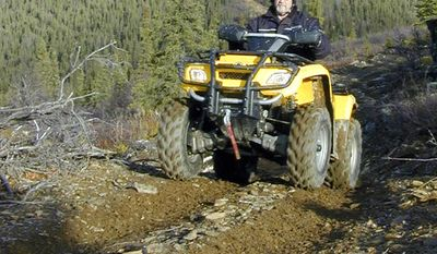 "This 2005 photo provided by the Alaska Department of Natural Resources shows then-Rep. Mike Kelly during a six-hour four-wheeler ride on a trail north of Two Rivers, Alaska, that had been made nearly impassible by state reclamation efforts. He called the trip ""miserable and ugly."" Through his efforts, state officials agreed to rework the trail and preserve it. Kelly died at 74 in December, 2016 when a plane he was piloting crashed. In March, 2017, Gov. Bill Walker announced he has renamed the 13.5-mile trail as the ""Mike Kelly Trail"" on maps and signage. (Tim Mowry/Alaska Department of Natural Resources via AP)"