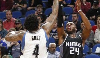 Sacramento Kings' Buddy Hield, right, of the Bahamas, releases a shot over Minnesota Timberwolves' Brandon Rush during the first half of an NBA basketball game Saturday, April 1, 2017, in Minneapolis. (AP Photo/Jim Mone)