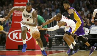 Los Angeles Clippers guard Chris Paul, center, reaches for the loose ball next to center DeAndre Jordan, left, and Los Angeles Lakers guard D'Angelo Russell, right, during the first half of an NBA basketball game, Saturday, April 1, 2017, in Los Angeles. (AP Photo/Ryan Kang)
