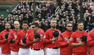 Members of the Washington Nationals line up on the field for the national anthem in front of Midshipmen in the stands before an exhibition baseball game against the Boston Red Sox at the U.S. Naval Academy in Annapolis, Md., Saturday, April 1, 2017. (AP Photo/Patrick Semansky)