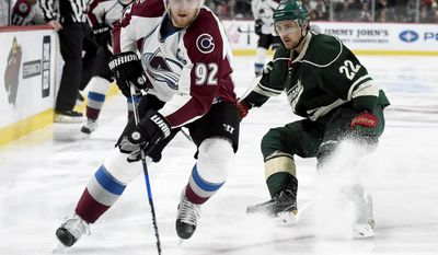 Colorado Avalanche left wing Gabriel Landeskog (92), of Sweden, has the puck against Minnesota Wild right wing Nino Niederreiter (22), of Switzerland, during the second period of an NHL hockey game Sunday, April 2, 2017, in St. Paul, Minn. (AP Photo/Hannah Foslien)