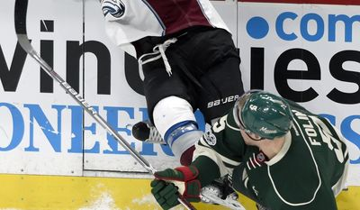 Minnesota Wild defenseman Christian Folin (5), of Sweden, and Colorado Avalanche left wing Blake Comeau (14), of Russia, crash into the boards during the first period of an NHL hockey game Sunday, April 2, 2017, in St. Paul, Minn. (AP Photo/Hannah Foslien)