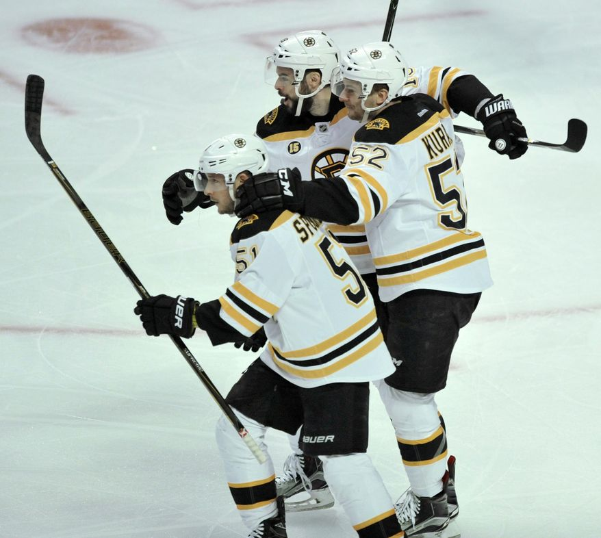Boston Bruins' Ryan Spooner (51) celebrates with teammates Sean Kuraly (52) and Drew Stafford (19) after scoring a goal during the first period of an NHL hockey game against the Chicago Blackhawks, Sunday, April 2, 2017, in Chicago.