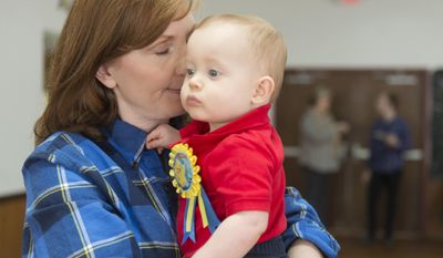 In this Saturday, March 11, 2017 photo, Lisa McCarter holds her grandson, Asher, at his first birthday celebration in Kodak, Tenn. For Lisa and Kevin McCarter, who lost their Gatlinburg home to the wildfire on Monday, Nov. 28, reasons to celebrate have been scarce. The recovery has been slow, but recently the couple had the opportunity to celebrate one of life's biggest milestones, the first birthday of their only grandchild, Asher. (Saul Young/Knoxville News Sentinel via AP)